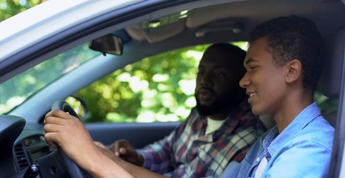 caring paren teaching son how to drive a car